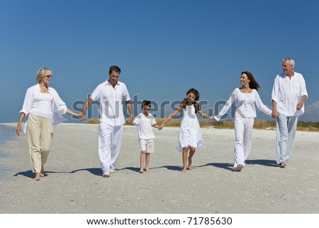 A happy family of grandparents, mother, father, two children, son and daughter, walking holding hands and having fun on a sunny beach - stock photo