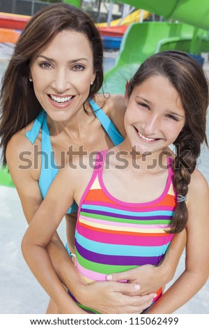 A happy family of mother and daughter, woman and girl child, having fun on vacation at a water park - stock photo