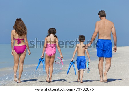 A happy family of mother, father and child, a daughter, walking in swimming costumes on a sunny beach - stock photo