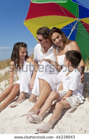 A happy family of mother, father and two children, son and daughter, laughing and having fun in the sand under a colorful umbrella or parasol on a sunny beach