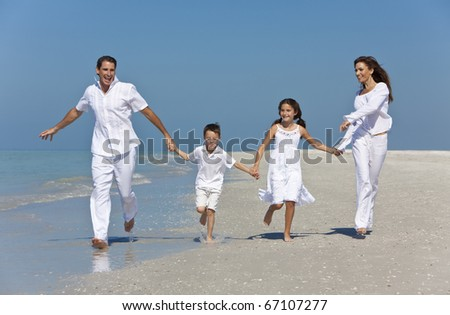 A happy family of mother, father and two children, son and daughter, running holding hands and having fun in the sand of a sunny beach - stock photo