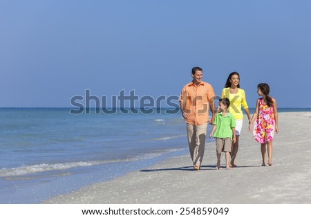 A happy family of mother, father and two children, son and daughter, walking and having fun in the sand of a deserted sunny beach - stock photo