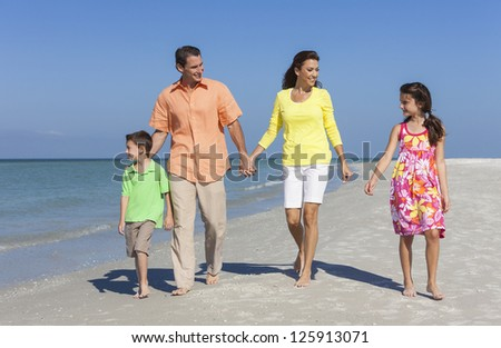 A happy family of mother, father and two children, son and daughter, walking holding hands and having fun in the sand of a deserted sunny beach