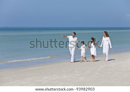 A happy family of mother, father and two children, son and daughter, walking holding hands and having fun in the sand on a sunny beach - stock photo