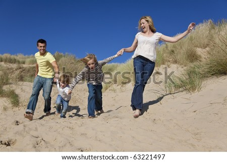A happy family of mother, father and two sons, running holding hands and having fun in the sand dunes of a sunny beach