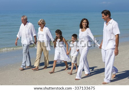 A happy family of mother, father, grandparents and two children, son and daughter, walking holding hands and having fun in the sand on a sunny beach