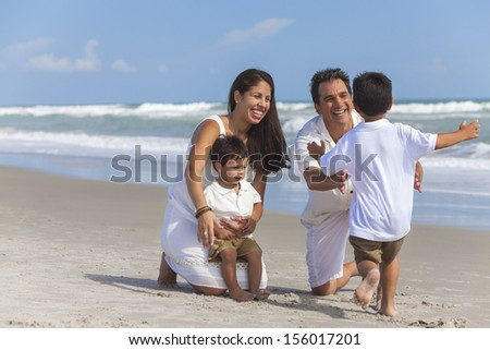 A happy family of mother, father parents & boy son children, playing and having fun on a sunny beach - stock photo