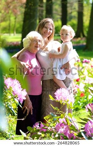 A happy family of three generations, mother, daughter, grandmother and little toddler granddaughter are enjoying together beautiful blossoming floral park on a sunny spring or summer day - stock photo