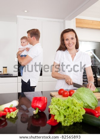 A happy family of three preparing supper in the kitchen - stock photo
