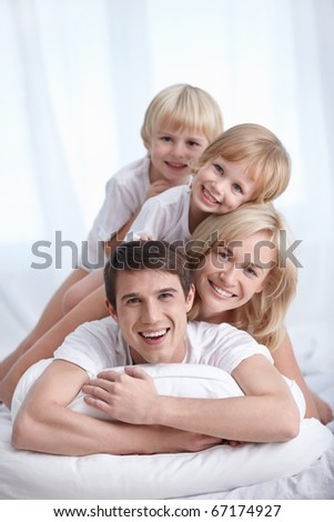 A happy family on a bed in the bedroom - stock photo