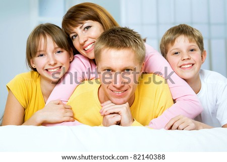 A happy family on bed in the bedroom - stock photo