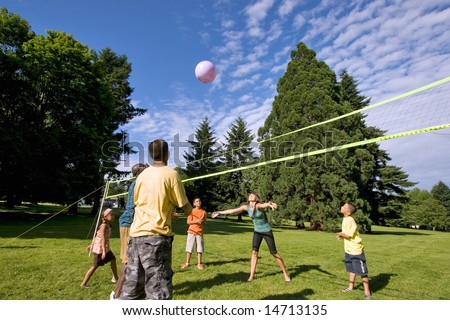 A happy family, playing volleyball together outdoors. - horizontally framed - stock photo