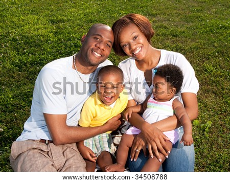 a happy family poses in a park