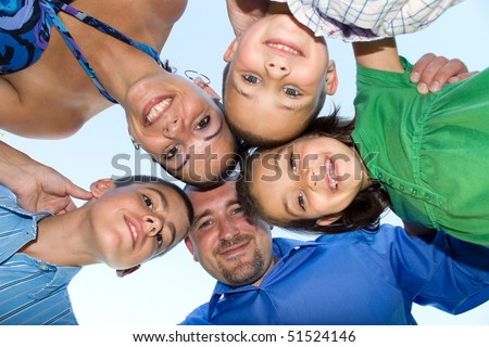A happy family posing in a group huddle formation.  Shallow depth of field. - stock photo