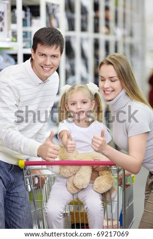 A happy family shows thumbs up at the store - stock photo
