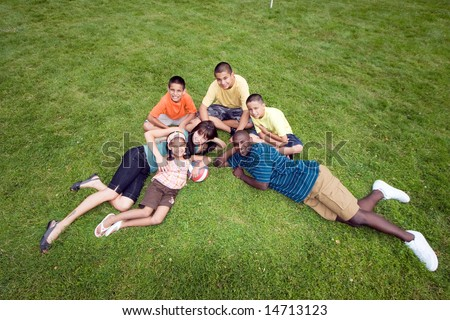 A happy family sit and lie in the grass, smiling. - horizontally framed - stock photo