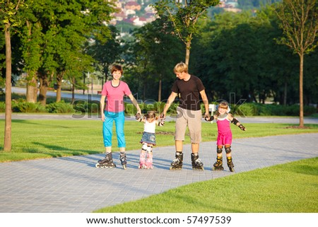 A happy family skating in a summer park - stock photo
