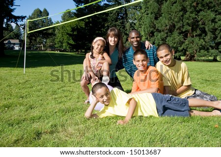 A happy family, together, smiling near a volleyball net. - horizontally framed - stock photo