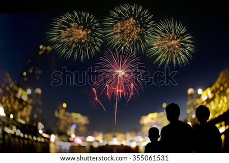 A happy family watching fireworks show over cityscape at night . - stock photo