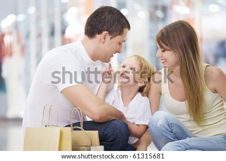 A happy family with a child in the store - stock photo