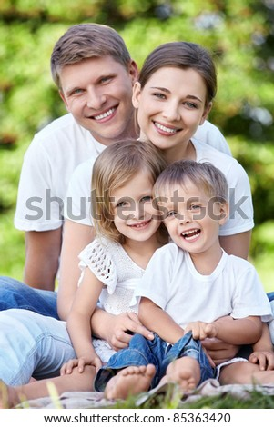 A happy family with kids in the park - stock photo