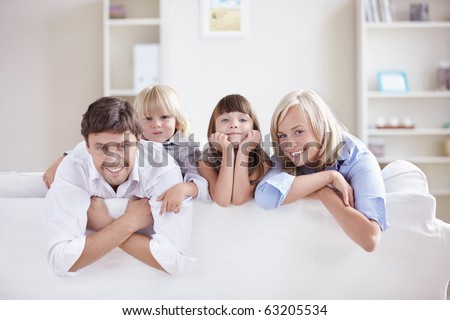 A happy family with kids on the couch - stock photo