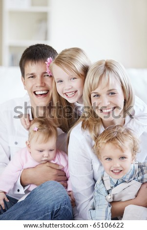 A happy family with kids on the couch at home - stock photo