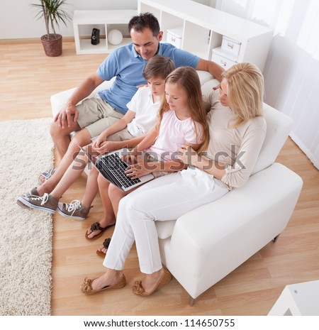A Happy Family With Two Children Sitting On A Sofa Using Laptop At Home - stock photo