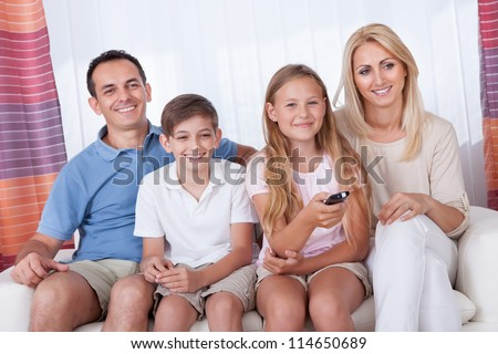 A Happy Family With Two Children Sitting On A Sofa Watching Tv At Home