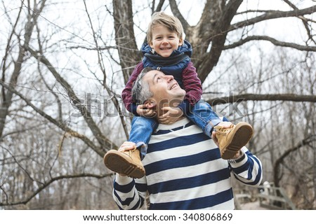A happy father and son having fun in park at the end of october