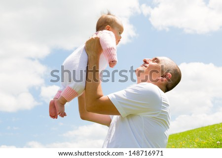 A happy father holds his baby daughter high in the air, with the bright cloudy sky in the background