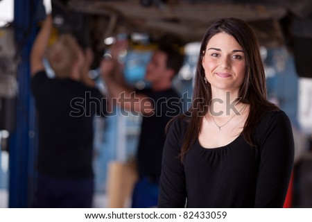 A happy female auto repair customer looking at the camera with a smile - stock photo