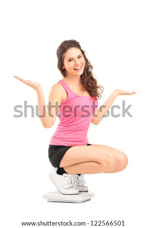 A happy female on a weight scale gesturing with her hands isolated against white background