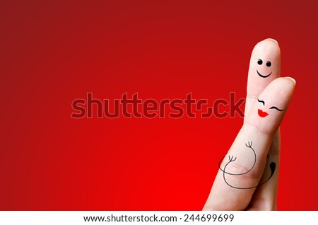 A happy finger couple in love; painted smiley and hugging - stock photo