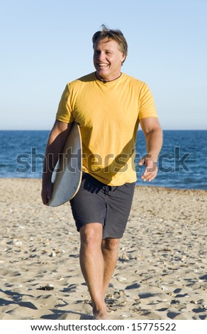 A happy forties man walking on beach with surboard. - stock photo