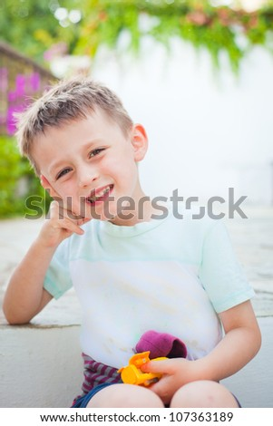 A happy four year old boy in a garden - stock photo
