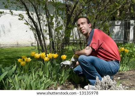 A happy gardener weeding the flower garden - stock photo