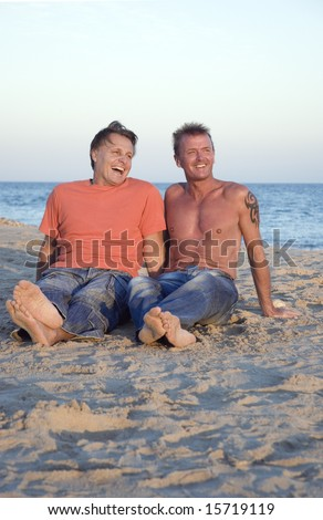 A happy gay couple are enjoying their vacation on the beach. - stock photo