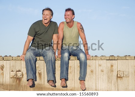 A happy gay couple are having fun together as they sit on the boardwalk at the beach. - stock photo