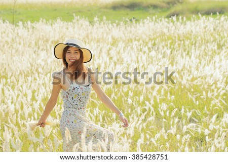 A happy girl at meadow in the early morning. Sun shine with golden light, silhouette back light on her body and grass flowers. Image create for people, healthcare, fashion and cosmetic. - stock photo