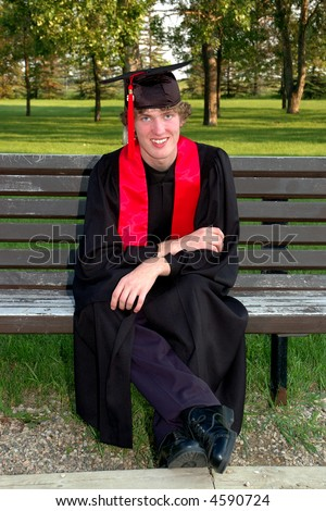 A happy graduate student in cap and gown sitting on park bench. - stock photo
