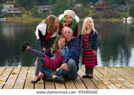 A happy Grandfather with a group of kids on a dock at a lake outside. - stock photo