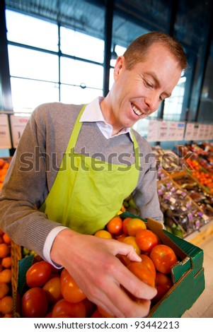 A happy grocery store owner looking over a box of ripe tomatoes - stock photo