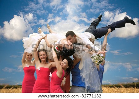 A happy groom and bride  tossed into sky by a group of friends - stock photo