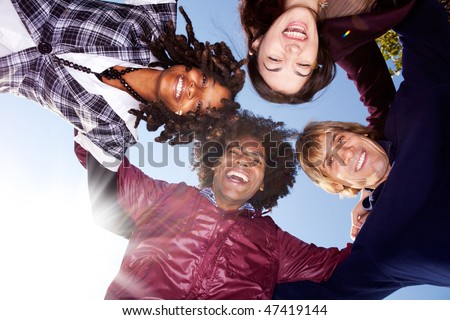 A happy group hug of friends - with solar flare from bottom left - stock photo