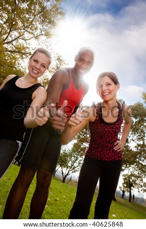 A happy group of people in the park exercising - stock photo