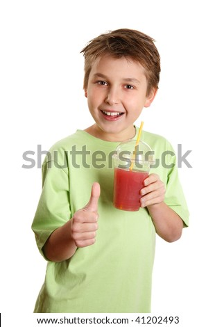 A happy, health conscious boy drinking fresh juice and showing a thumbs up sign. - stock photo