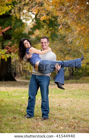 A happy healthy couple in the park - Man holding the Woman - stock photo