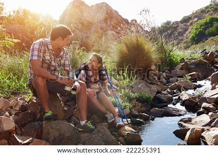 A happy hiking couple sitting by a dam in a nature reserve - stock photo