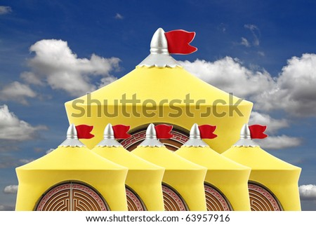 A happy image of a group of yellow castle top with red flag flying against a blue cloudy sky. - stock photo